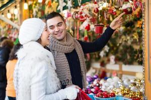 jonge man met vriendin op kerstmarkt foto