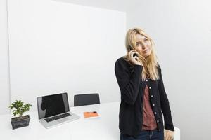 zakenvrouw antwoordende mobiele telefoon in kantoor foto