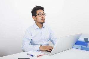 doordachte zakenman met laptop zitten aan de balie in kantoor foto