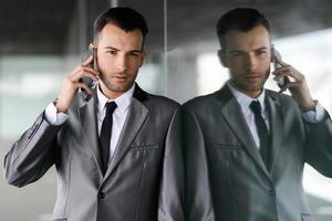 aantrekkelijke jonge zakenman aan de telefoon in een kantoorgebouw foto