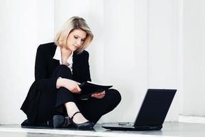 jonge zakenvrouw met behulp van laptop op de stoep foto