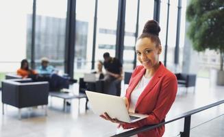 mooie jonge Afrikaanse vrouw met laptop in het moderne kantoor foto