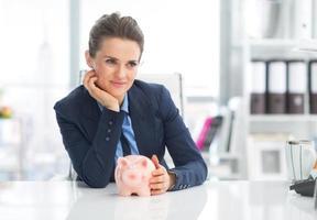 doordachte zakenvrouw met spaarvarken foto