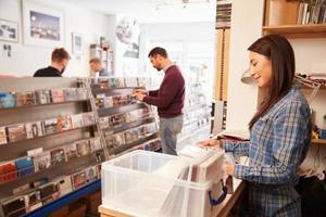 vrouw die achter de balie bij een platenwinkel werkt foto