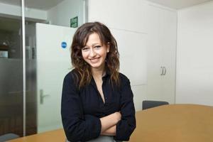 trotse zakenvrouw zitten in haar bestuurskamer foto