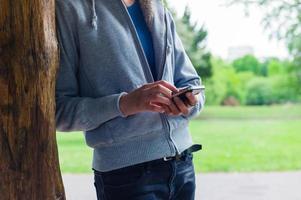 vrouw die haar smartphone in het park gebruiken foto