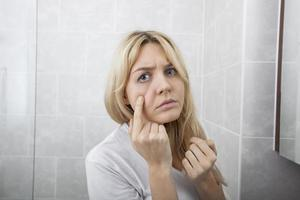 jonge vrouw die puistjes op gezicht in badkamers onderzoekt foto