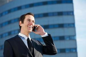 gelukkig zakenman glimlachend en praten op mobiele telefoon buitenshuis foto