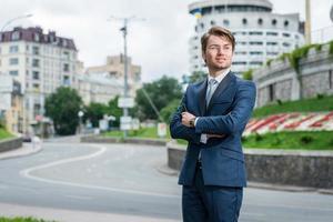 jonge man in formele kleding staat naast de weg foto