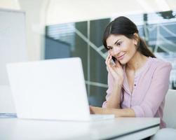 jonge zakenvrouw met behulp van mobiele telefoon tijdens het kijken naar laptop foto