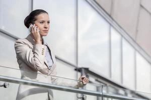 zelfverzekerde jonge zakenvrouw met behulp van slimme telefoon op kantoor reling foto
