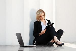 jonge zakenvrouw met laptop zittend aan de muur foto
