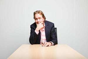 zakenman met blond haar zitten verveeld achter bureau. foto