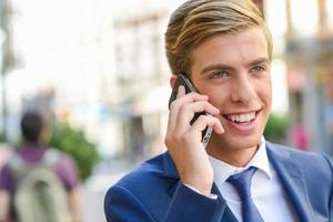 aantrekkelijke jonge zakenman aan de telefoon op stedelijke achtergrond foto