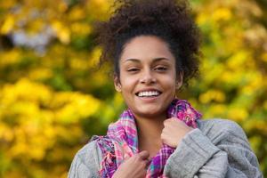 aantrekkelijke jonge Afro-Amerikaanse vrouw die lacht in de herfst