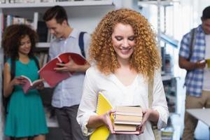 student die kleine stapel boeken draagt foto