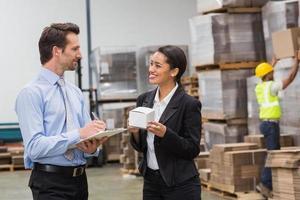 glimlachende pakhuismanagers die doos en klembord houden
