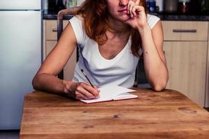 verveeld vrouw schrijven in haar keuken foto