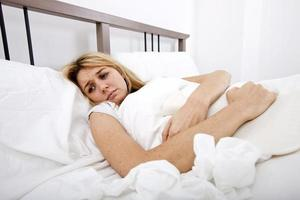 vrouw die lijden aan buikpijn in bed foto