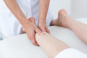 fysiotherapeut die beenmassage doet foto