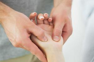 sluit omhoog van fysiotherapeut die de hand van patiënten masseert foto