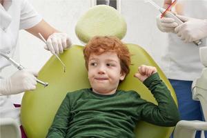 kleine schattige jongen zittend in de stoel bij de tandarts foto