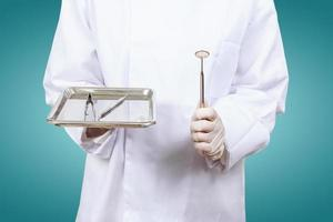 hand van tandarts of tandartsassistenten. houd tandartsen tools. foto