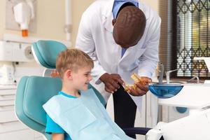 tandarts die de tandheelkundige procedure uitlegt foto