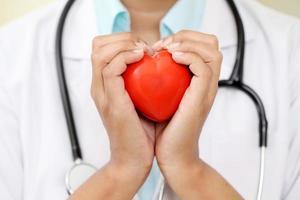 vrouwelijke arts die een mooie rode hartvorm houdt foto