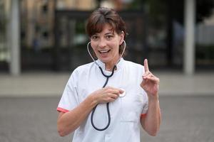 glimlachende cardioloog die aan haar hart luistert foto