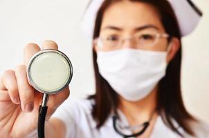 verpleegster in gezichtsmasker met stethoscoop foto