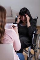 vrouw op rolstoel praten met therapeut foto