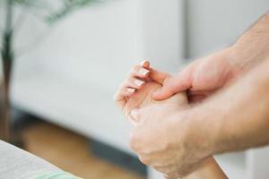 fysiotherapeut die de hand van een patiënt masseert foto