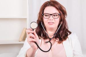 jonge vrouwelijke arts met een stethoscoop onderzoeken foto