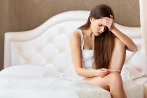 zwangerschaptest. bezorgd vrouw kijken naar een test