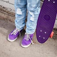 tiener in blauwe jeans staat met skateboard