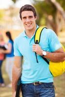 mannelijke universiteitsstudent buitenshuis foto