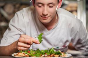 mannelijke kok die heerlijk voorgerecht voorbereidt foto