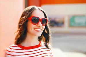 portret van vrij lachende vrouw in rode zonnebril buitenshuis foto