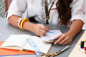 close-up van volwassen vrouwelijke naaister die wat kledingontwerp drowing foto