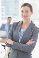 Glimlachende zakenvrouw met collega's achter foto