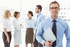 glimlachende zakenman met erachter collega's