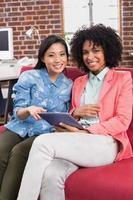 casual collega's met behulp van digitale tablet op Bank