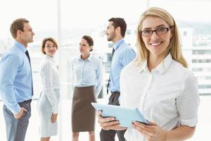 zakenvrouw met behulp van digitale tablet met collega's achter
