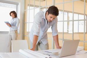 zakenman die laptop met collega op achtergrond met behulp van