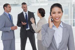 zakenvrouw aan de telefoon terwijl collega's praten