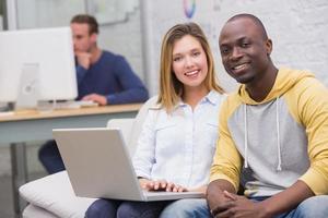casual collega's met behulp van laptop op bank in kantoor foto