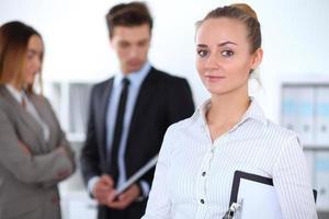 mooie zakenvrouw in kantoor met collega's op de achtergrond foto