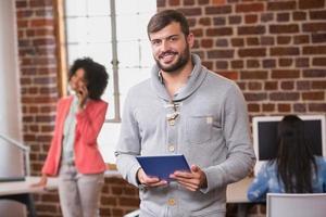 man met behulp van digitale tablet met collega achter in office foto