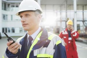 mannelijke werknemer met behulp van walkie-talkie met collega op achtergrond